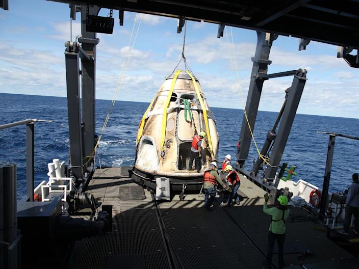 Crew Dragon is loaded onto the SpaceX's recovery ship, Go Searcher, in the Atlantic Ocean about 200 miles off Florida's east coast on March 8.