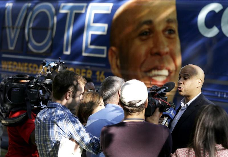 Newark Mayor Cory Booker, right, talks to reporters near his tour bus while visiting supporters at a senior center, Tuesday, Oct. 15, 2013, in Newark, N.J. Booker will be going up against his Republican opponent Steve Lonegan Wednesday, Oct. 16, during a special election to fill New Jersey's vacant seat in the U.S. Senate. (AP Photo/Julio Cortez)