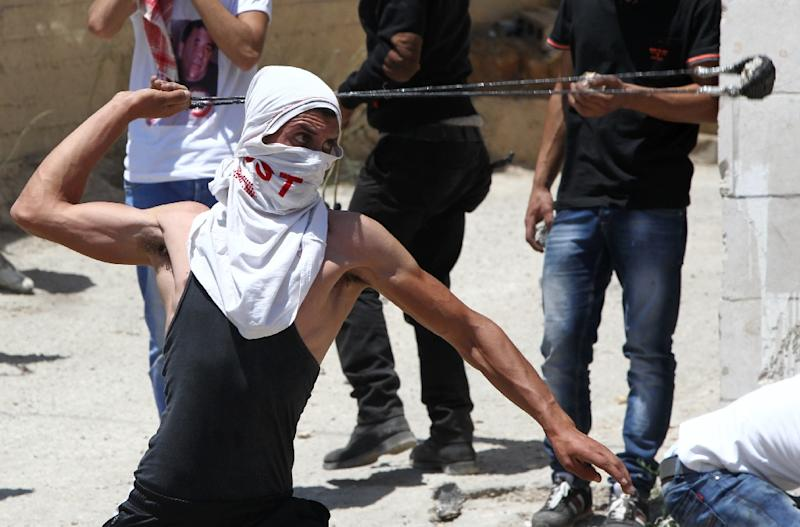 A Palestinian protester throw stones using a slingshot towards members of the Israeli security forces during clashes following the funeral of Falah Abu Maria in Beit Omar, near the southern city of Hebron, on July 23, 2015 (AFP Photo/Hazem Bader)