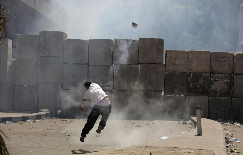 An Egyptian protester throws back a tear gas canister toward riot police, unseen, behind cement blocks that are used to close the street leading to the U.S. embassy during clashes in Cairo, Egypt, Friday, Sept. 14, 2012, as part of widespread anger across the Muslim world about a film ridiculing Islam's Prophet Muhammad. (AP Photo/Nasser Nasser)