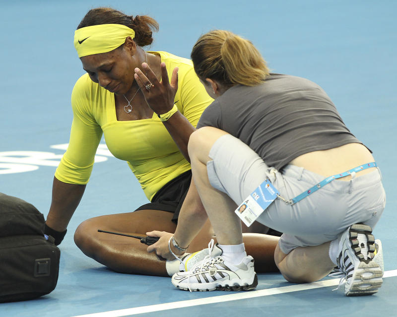 Serena Williams of the United States receives medical attention after twisting her left ankle in her match against Bojana Jovanovski of Serbia during the Brisbane International tennis tournament in Brisbane, Australia, Wednesday, Jan. 4, 2012.  (AP Photo/Tertius Pickard)