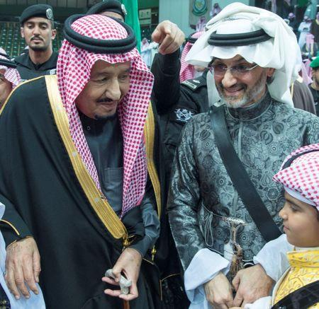 FILE PHOTO: Saudi Arabia's King Salman bin Abdulaziz Al Saud stands next to Saudi Arabian billionaire Prince Alwaleed bin Talal (R) during a ceremony of the traditional Ardha sword dance as part of the activities of Janadriyah Culture festival, in Riyadh, Saudi Arabia February 20, 2018. Bandar Algaloud/Courtesy of Saudi Royal Court/Handout via REUTERS