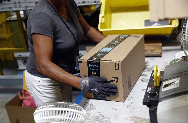 In this Aug. 3, 2017, photo, Myrtice Harris applies tape to a package before shipment at an Amazon fulfillment center in Baltimore. While jobs have been lost in brick-and-mortar stores, many more have been gained from e-commerce and warehousing. Amazon accounts for much of the additional employment. (AP Photo/Patrick Semansky)