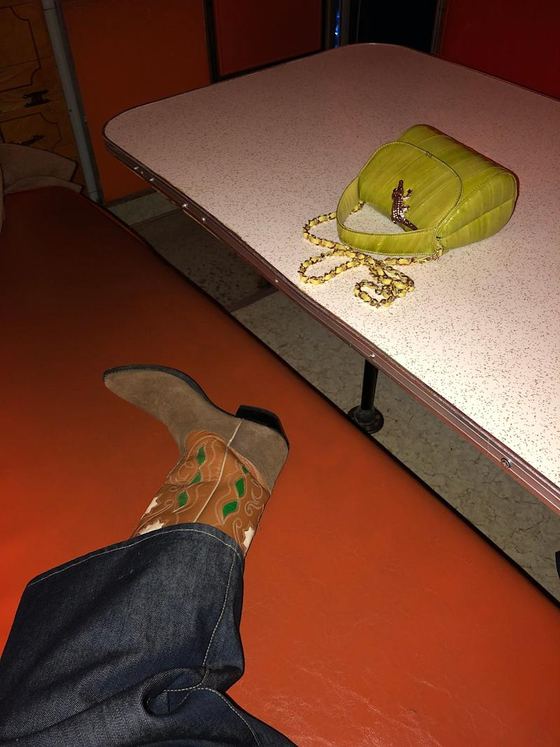 """The weirdest place I've ever been, """"The House of Eternal Return,"""" in Santa Fe. There are dozens of rooms, secret passages, and interactive light and musical objects. With my vintage cowboy boots, my apple green tiny bag, and my Eve Denim pant."""