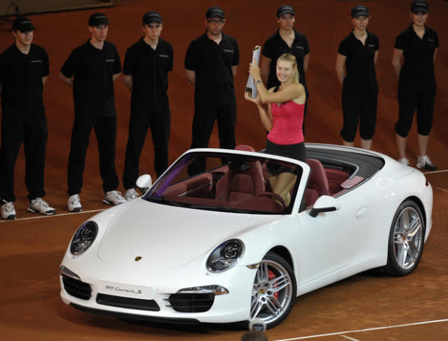 Russia's Maria Sharapova poses for photographers in the winner's prize, a Porsche 911 Carrera, after defeating Belarus` Victoria Azarenka in the final match of the WTA Porsche Tennis Grand Prix in Stuttgart, southwestern Germany, on April 29, 2012. Sharapova won 6-1, 6-4. AFP PHOTO THOMAS KIENZLETHOMAS KIENZLE/AFP/GettyImages