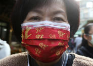 """A woman wears a Chinese auspicious character """"Fu (good fortune)""""-patterned mask to help curb the spread of the coronavirus as they shop at a market in Taipei, Taiwan, Monday, Jan. 25, 2021. (AP Photo/Chiang Ying-ying)"""