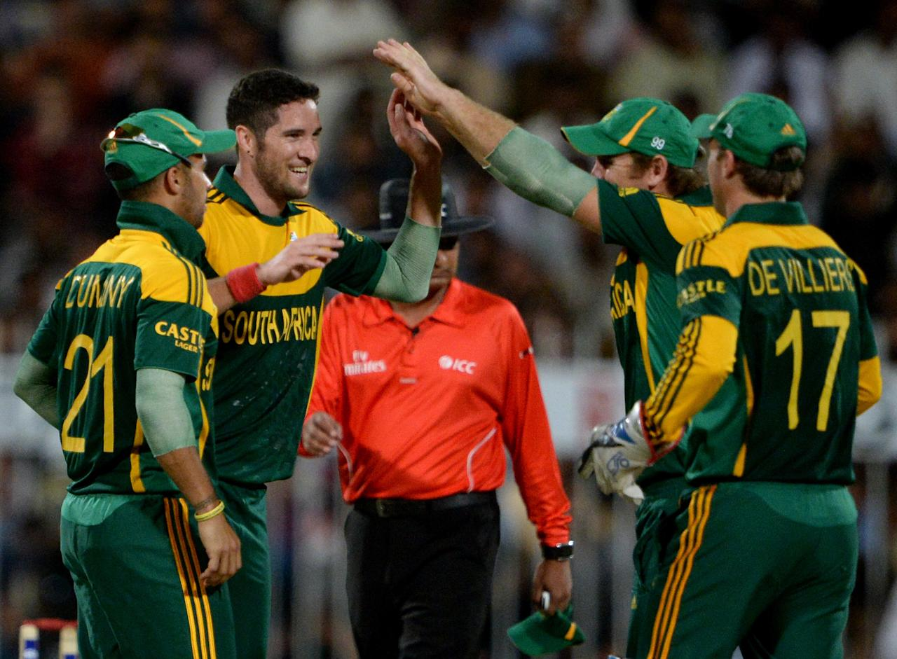 South African bowler Wayne Parnell (2nd L) celebrates with teammates after taking a wicket of Pakistan's captain Misbah ul Haq (unseen) during the first one-day in Sharjah Cricket Stadium in Sharjah on October 30, 2013. South African captain AB de Villiers won the toss and decided to bat in the first of five one-day internationals against Pakistan in Sharjah. AFP PHOTO/ASIF HASSAN        (Photo credit should read ASIF HASSAN/AFP/Getty Images)