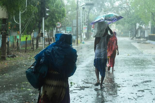 Residents walk along a street to a shelter ahead of the expected landfall of cyclone Amphan in Digha. (Photo by Dibyangshu SARKAR / AFP)