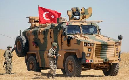FILE PHOTO: A Turkish soldier walks next to a Turkish military vehicle during a joint U.S.-Turkey patrol, near Tel Abyad