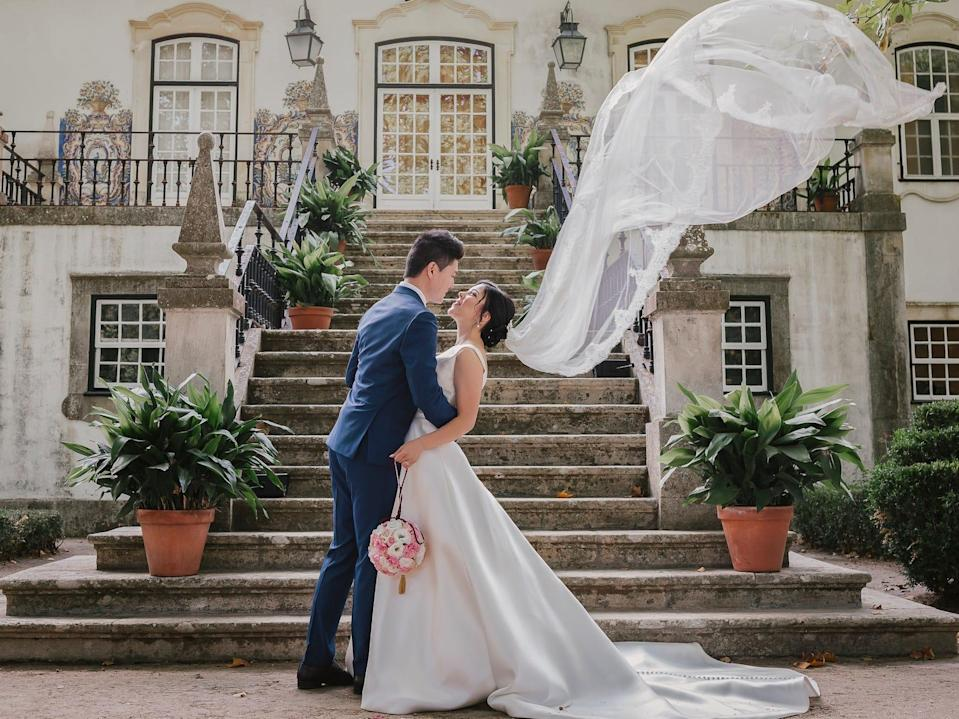 A bride and groom embrace in front of a grand staircase. The bride's veil sweeps upwards dramatically.