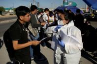 Personnel of an assembly factory, in protective gear, talk to job seekers as the coronavirus disease (COVID-19) outbreak continues in Ciudad Juarez