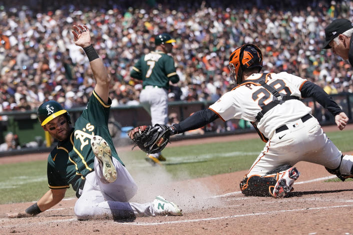 Oakland Athletics' Chad Pinder, left, scores past San Francisco Giants catcher Buster Posey (28) during the sixth inning of a baseball game in San Francisco, Sunday, June 27, 2021. (AP Photo/Jeff Chiu)