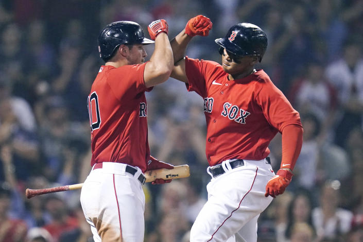 Boston Red Sox's Rafael Devers, right, is congratulated by Hunter Renfroe after his solo home run in the third inning of a baseball game against the Toronto Blue Jays at Fenway Park, Monday, July 26, 2021, in Boston. (AP Photo/Charles Krupa)
