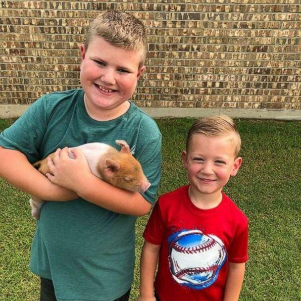 PHOTO: Jase (left) and Boden (right) pose with piglet named Dynamite. (Cashlie Joy Photography)