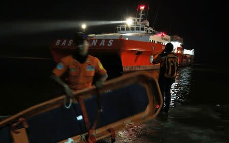 A Search and Rescue team member carries a stretcher as he gets ready to board SAR ship Purworejo for search operations for passengers onboard AirAsia flight QZ8501 at Kumai port, Pangkalan Bun district December 31, 2014. REUTERS/Beawiharta