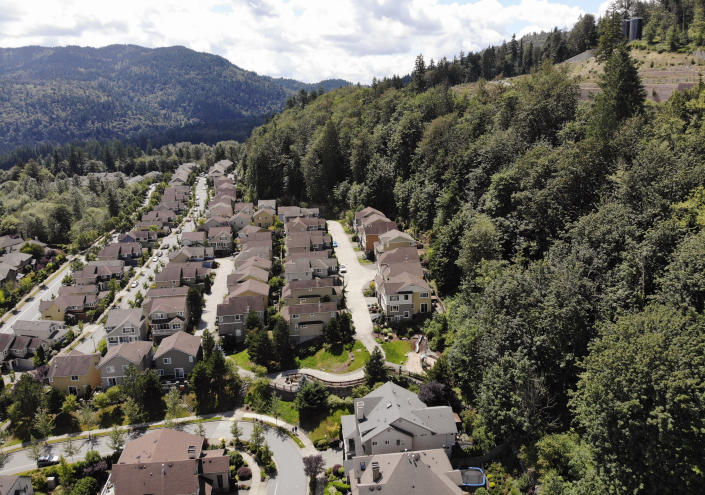 In this photo taken July 24, 2019, houses stand adjacent to a forest in the Seattle suburb of Issaquah, Wash. Experts say global warming is changing the region's seasons, bringing higher temperatures, lower humidity and longer stretches of drought. And that means wildfire risks in coming years will extend into areas that haven't experienced major burns in residents' lifetimes. (AP Photo/Elaine Thompson)