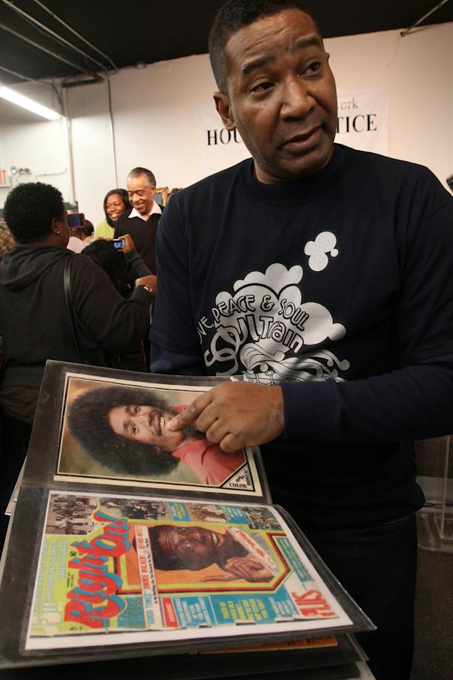 """Tyrone Proctor shows a picture of himself from the time when he was a """"Soul Train"""" dancer as he is interviewed following a tribute to """"Soul Train"""" creator Don Cornelius at Rev. Al Sharpton's National Action Network in New York Saturday, Feb. 4, 2012. Cornelius died this week at his Los Angeles home of a self-inflicted gunshot wound. He was 75. (AP Photo/Tina Fineberg)"""
