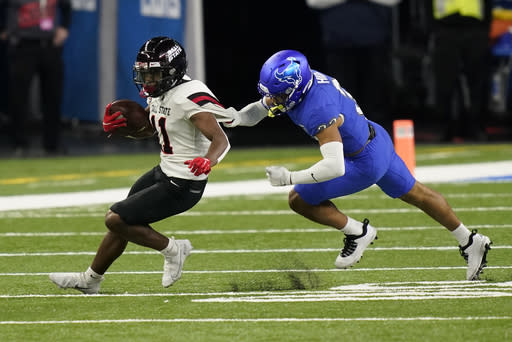 Ball State wide receiver Justin Hall (11) pulls away from Buffalo safety Tyrone Hill (33) during the first half of the Mid-American Conference championship NCAA college football game, Friday, Dec. 18, 2020 in Detroit. (AP Photo/Carlos Osorio)
