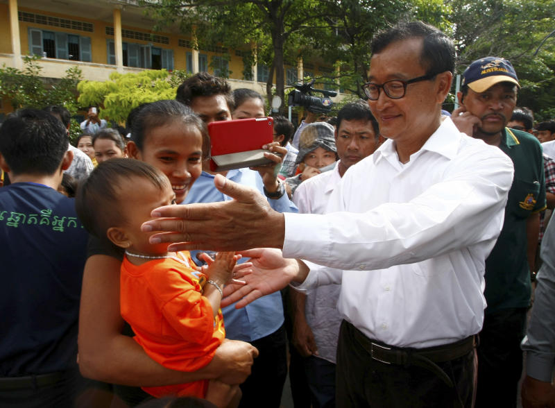 Sam Rainsy, leader of Cambodia National Rescue Party, touches a baby's face while visiting a polling station at Chak Angre Leu pagoda, in Phnom Penh, Cambodia, Sunday, July 28, 2013. Cambodians began voting across the country Sunday to take part in what has become a familiar ritual - the re-election of Prime Minister Hun Sen, who has been on the job for 28 years and says he hopes to rule for at least another decade. (AP Photo/Heng Sinith)
