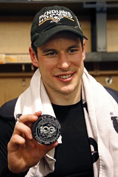 Pittsburgh Penguins' Sidney Crosby holds the puck honoring the 1,000th point in his NHL career, in the locker room after scoring in overtime of the team's NHL game against the Winnipeg Jets in Pittsburgh, Thursday, Feb. 16, 2017. Crosby had an assist on a goal by Penguins' Chris Kunitz in the first period to reach 1,000 points. (AP Photo/Gene J. Puskar)