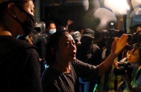 A pro-government supporter argues with anti-government protesters during a demonstration in Tin Shui Wai in Hong Kong