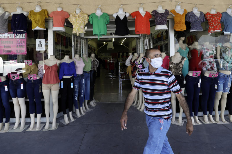 A man passes a clothing shop Tuesday, June 30, 2020, in Calexico, Calif. Saddled with a surge in positive cases and hospitalizations for the new coronavirus, a farming region on California's border with Mexico is now forced to backpedal on reopening its battered economy. The Imperial County board of supervisors unveiled a plan late Monday that includes closing businesses deemed non-essential, except for curbside pickup, and shuttering county parks. (AP Photo/Gregory Bull)