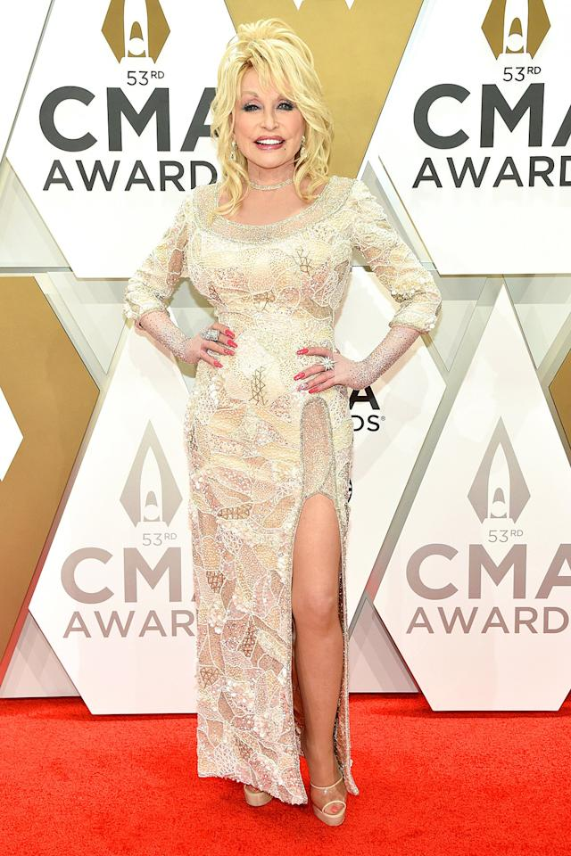 brings her iconic fashion sense to the red carpet in a heavily-embellished off-white gown featuring a daring high slit, plus platform shoes and lots of bling.