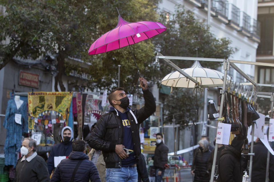 A stall-holder sets up his display in the Rastro flea market in Madrid, Spain, Sunday, Nov. 22, 2020. Madrid's ancient and emblematic Rastro flea market reopened Sunday after a contentious eight-month closure because of the COVID-19 pandemic that has walloped the Spanish capital. (AP Photo/Paul White)