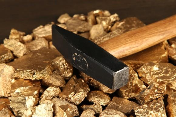 A hammer on a pile of gold