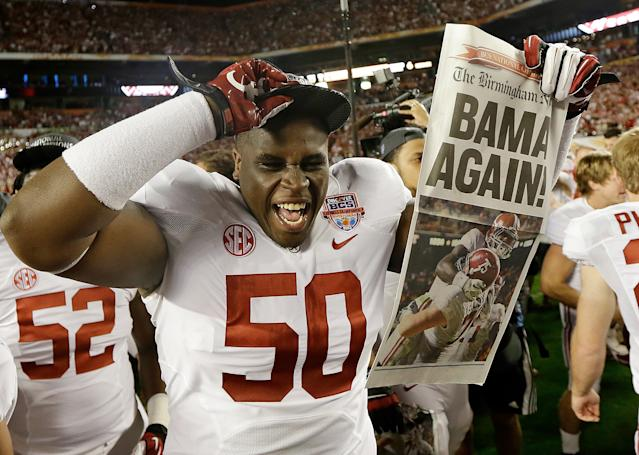 Alabama defensive lineman Alphonse Taylor (50) holds up a newspaper after the BCS National Championship college football game Monday, Jan. 7, 2013, in Miami. Alabama won 42-14. (AP Photo/David J. Phillip)