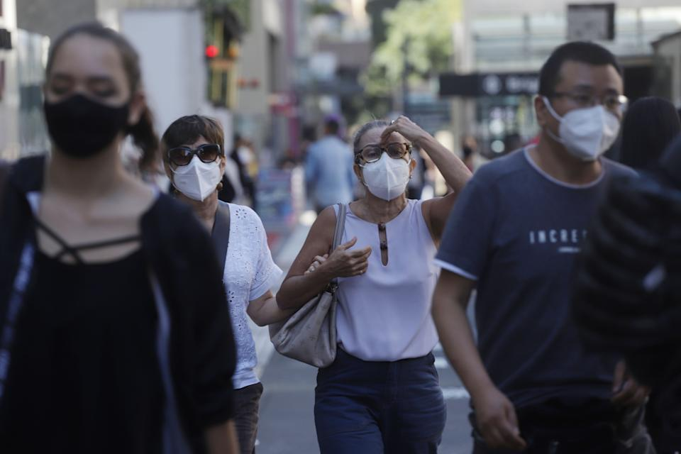 SAO PAULO, May 4, 2021 -- People wearing face masks walk on the street in Sao Paulo, Brazil, on May 4, 2021. Brazil reported on Tuesday 77,359 new COVID-19 cases, raising the total number of infections to 14,856,888. (Photo by Rahel Patrasso/Xinhua via Getty) (Xinhua/Rahel Patrasso via Getty Images)