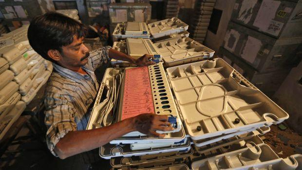 An image of a member of election duty staff arranging an EVM inside a strong room