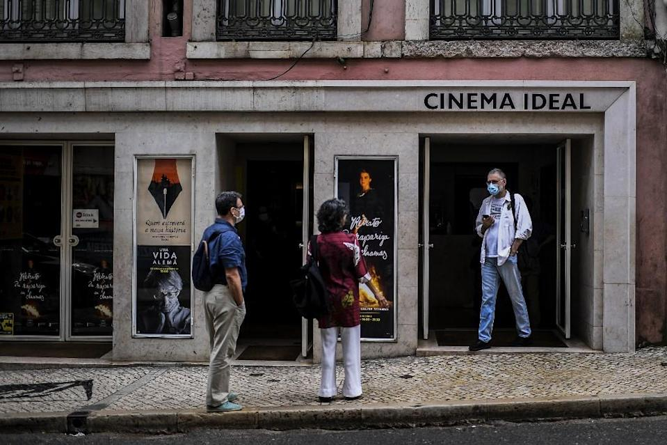 People wearing face masks wait for watching a movie at the Cinema IDEAL in Lisbon on June 1, 2020.