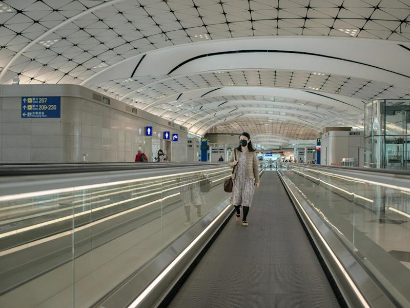 A passenger wears a surgical mask at an empty departure terminal hall at the Hong Kong International Airport.
