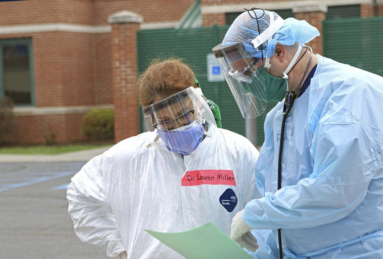 """Dr. Lauren Miller, left, and Dr. Micah Moore look over notes at a Mobile Health Unit for drive-thru coronavirus testing at Robert C. Byrd Clinic on the campus of the West Virginia School of Osteopathic Medicine in Lewisburg, W.Va., Tuesday, March 24, 2020. The nurses and doctors can test for COVID-19, but also treat flu and allergy symptoms.  """"It's a full medical appointment from the comfort of your own car,"""" Miller said. (Jenny Harnish/The Register-Herald via AP)"""