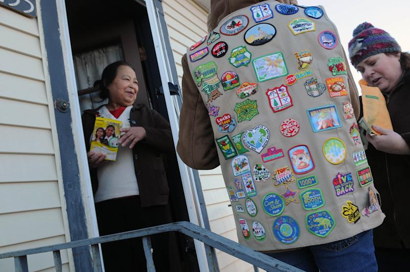 FILE - In this Feb. 12, 2012 file photo, a Girl Scout, wearing her vest covered in badges, sells a box of cookies to Paa Yang, left, a neighbor in Minneapolis. Long a lightning rod for conservative criticism, the Girl Scouts of the USA are now facing their highest-level challenge yet: An official inquiry by the U.S. Conference of Catholic Bishops. At issue are concerns about program materials that some Catholics find offensive, as well as assertions that the Scouts associate with other groups espousing stances that conflict with church teaching. The Scouts, who have numerous parish-sponsored troops, deny many of the claims and defend their alliances. But there's frustration within the iconic youth organization - known for its inclusiveness and cookie sales - that it has become such an ideological target, with the girls sometimes caught in the political crossfire. (AP Photo/The St. Paul Pioneer Press, Scott Takushi)