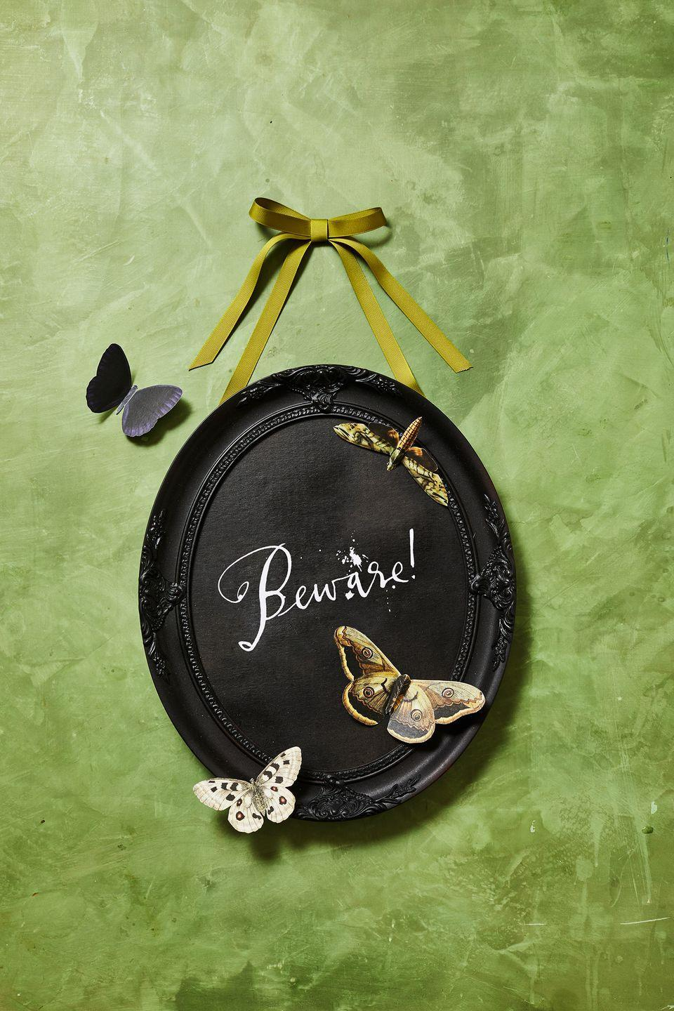 """<p>Coat a vintage frame in black spray paint and let it dry. Print butterfly images and Halloween-appropriate calligraphy art (think """"Beware!"""") on card stock. Cut them out and place them on your frame. Use ribbon to hang your new creation.</p><p><a class=""""link rapid-noclick-resp"""" href=""""https://www.goodhousekeeping.com/holidays/halloween-ideas/a33564450/gh-halloween-artwork-calligraphy-templates/"""" rel=""""nofollow noopener"""" target=""""_blank"""" data-ylk=""""slk:GET TEMPLATES"""">GET TEMPLATES </a></p>"""