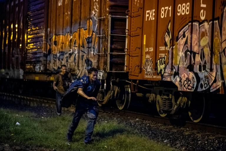 A migrant runs next to the freight train heading toward the US border