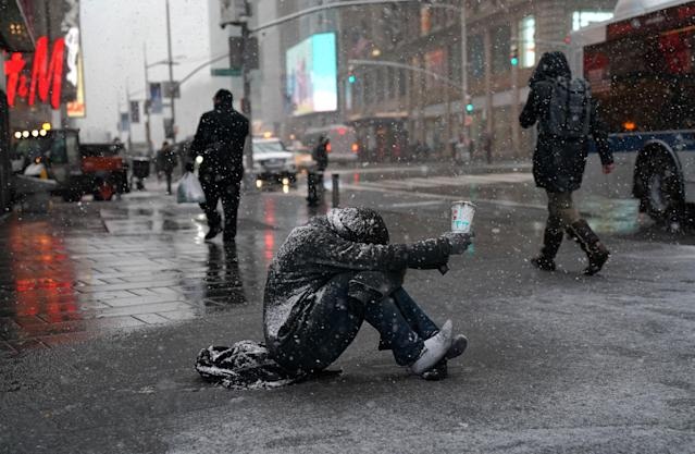 <p>A man begs for money in the snow along 42nd Street in Times Square in New York on March 21, 2018, as the fourth nor'easter in a month hits the tri-state area on the first full day of spring. (Photo: Timothy A. Clary/AFP/Getty Images) </p>
