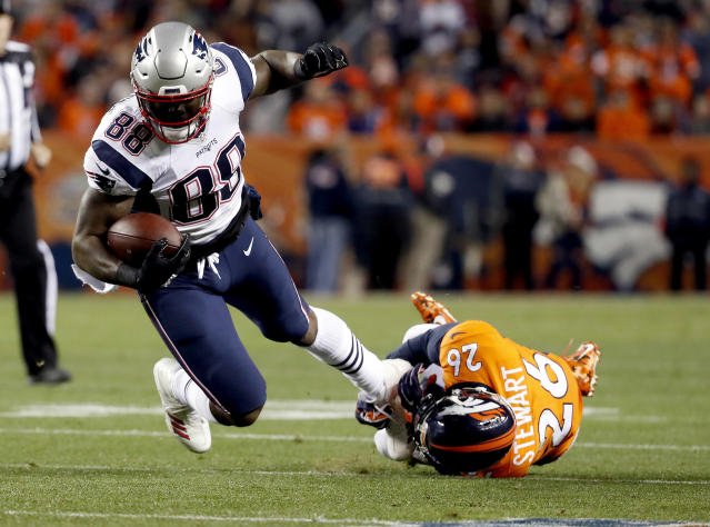FILE - In this Sunday, Nov. 12, 2017, file photo, New England Patriots tight end Martellus Bennett (88) is tripped up by Denver Broncos free safety Darian Stewart (26) during the first half of an NFL football game in Denver. Bennett is still coming to terms with how his Green Bay tenure ended. But he says being back in familiar surroundings is helping him to deal with it. (AP Photo/Jack Dempsey, File)