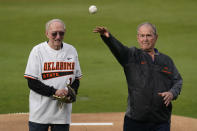 """FILE - In this May 20, 2021 file photo, former President George W. Bush, right, throws out a ceremonial first pitch next to Cecil O'Brate, left, before an NCAA college baseball game between New Orleans and Oklahoma State in O'Brate Stadium in Stillwater, Okla. The War on Terrorism begat the wars in Iraq and Afghanistan, and Bush's demand that the Taliban """"hand over the terrorists, or ... share in their fate."""" He had long retired to oil painting in Texas when Navy SEALs killed bin Laden, and when President Joe Biden pulled U.S. forces from Afghanistan. In August, he said he was watching developments there """"with deep sadness."""" (AP Photo/Sue Ogrocki)"""