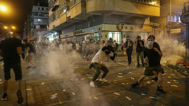 Hong Kong officers used tear gas against protesters after some pointed lasers at the police station