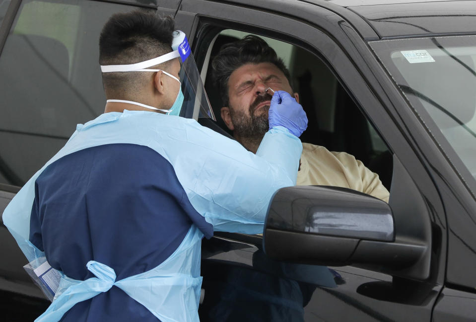 A man receives a COVID-19 test at a drive through testing station at a beach in Sydney, Australia, Saturday, Dec. 19, 2020. Sydney's northern beaches will enter a lockdown similar to the one imposed during the start of the COVID-19 pandemic in March as a cluster of cases in the area increased to more than 40. (AP Photo/Mark Baker)