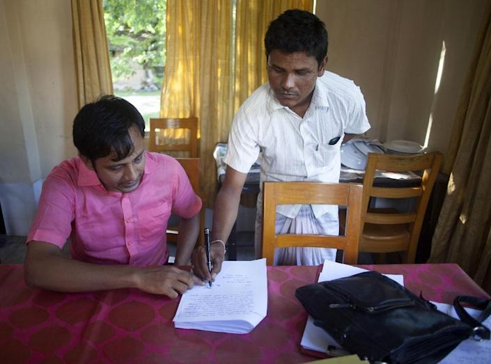 Bangladeshi citizen Mohammad Moinul (right) signs papers cancelling his application to migrate to India (AFP Photo/Suvra Kanti Das)