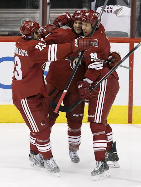 Phoenix Coyotes' Kyle Chipchura (24) celebrates his goal against the New York Rangers with teammates Oliver Ekman-Larsson (23), of Sweden, and David Moss (18) in the first period during an NHL hockey game on Thursday, Oct. 3, 2013, in Glendale, Ariz. (AP Photo/Ross D. Franklin)