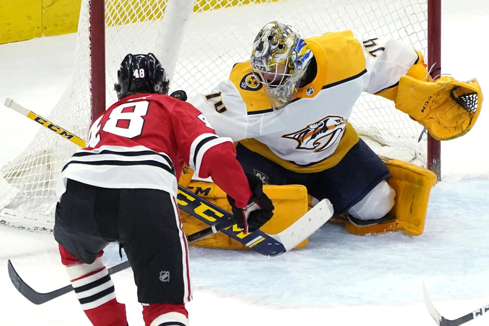 Chicago Blackhawks' Wyatt Kalynuk (48) scores past Nashville Predators goaltender Juuse Saros during the third period of an NHL hockey game Wednesday, April 21, 2021, in Chicago. (AP Photo/Charles Rex Arbogast)