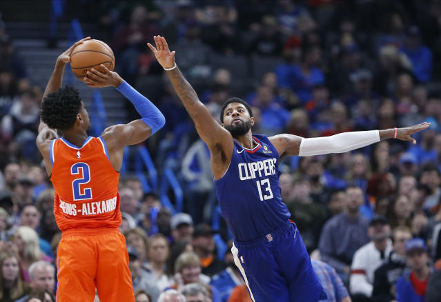 Los Angeles Clippers forward Paul George (13) defends a shot by Oklahoma City Thunder guard Shai Gilgeous-Alexander (2) during the second half of an NBA basketball game, Sunday, Dec. 22, 2019, in Oklahoma City. Oklahoma City won 118-112. (AP Photo/Alonzo Adams)