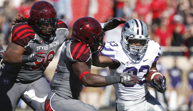 Texas Tech's Dennell Wesley, left, and Sam Eguavoen (13) try to stop Kansas State's John Hubert (33) during the first half of an NCAA college football game in Lubbock, Texas, Saturday, Nov. 9, 2013. (AP Photo/Lubbock Avalanche-Journal,Stephen Spillman)