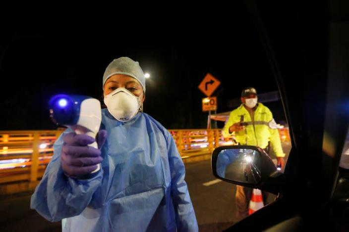 An Ecuadorian health official uses a thermal scanner on car passengers at Rumichaca International Bridge after Ecuador's government closed its borders to all foreign travelers due to the spread of the coronavirus disease, in Tulcan