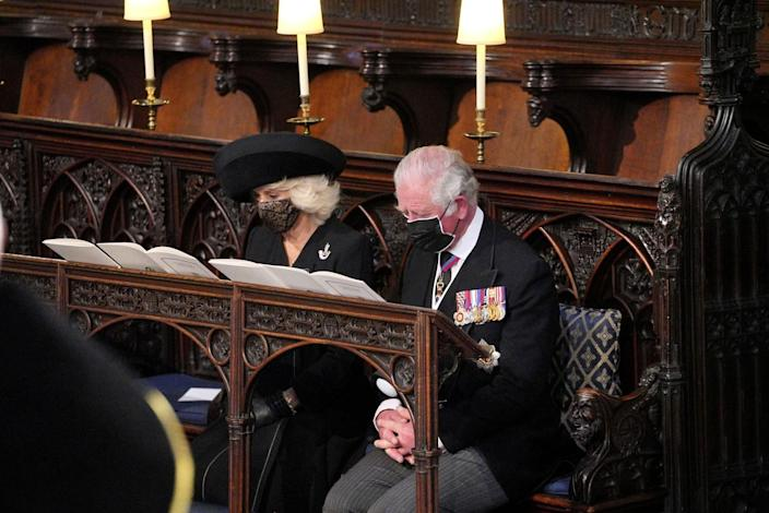 Prince Charles and Camilla sit in masks in St. George's Chapel.
